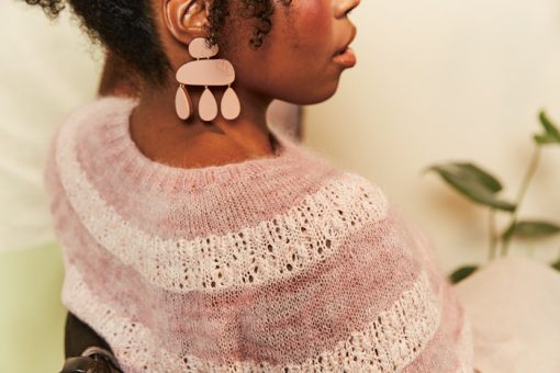 black woman in wheelchair modelling pink striped lace sweater