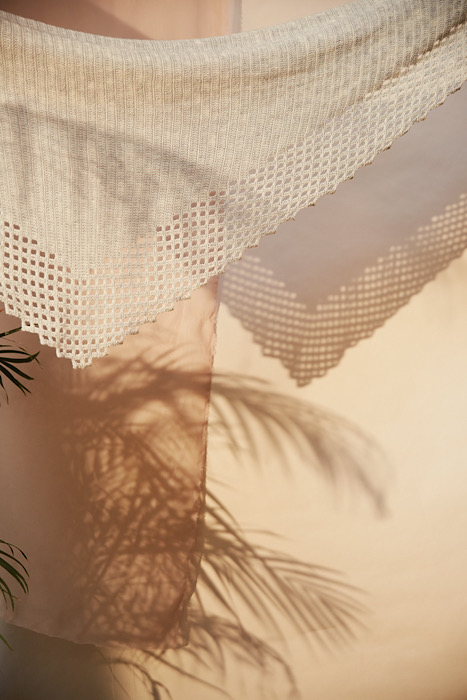 a knitted triangle shawl in front of a pink wall with the shadow of a palm and the shawl
