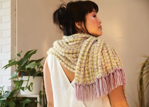 woman modelling a yllow white scarf with long lilac tassles while looking over her shoulder