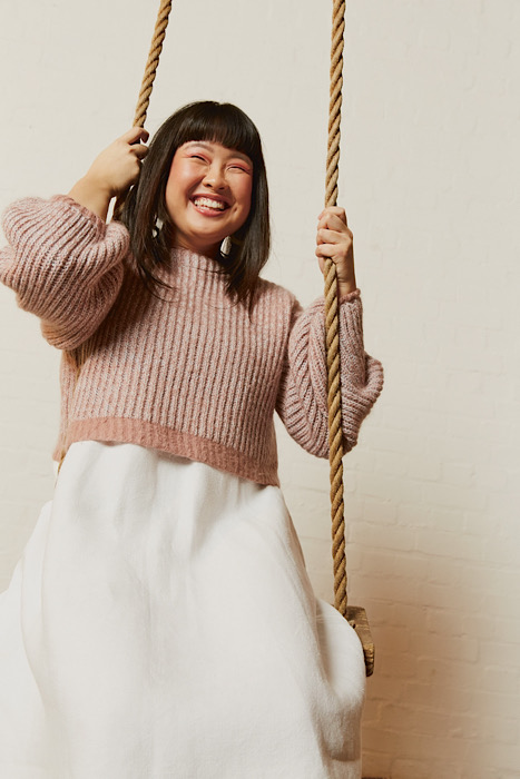 laughing lady on a swing modelling a pink knitted sweater