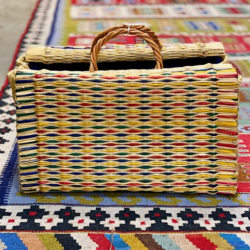 CESTA reed project basket on colourful carpet on floor