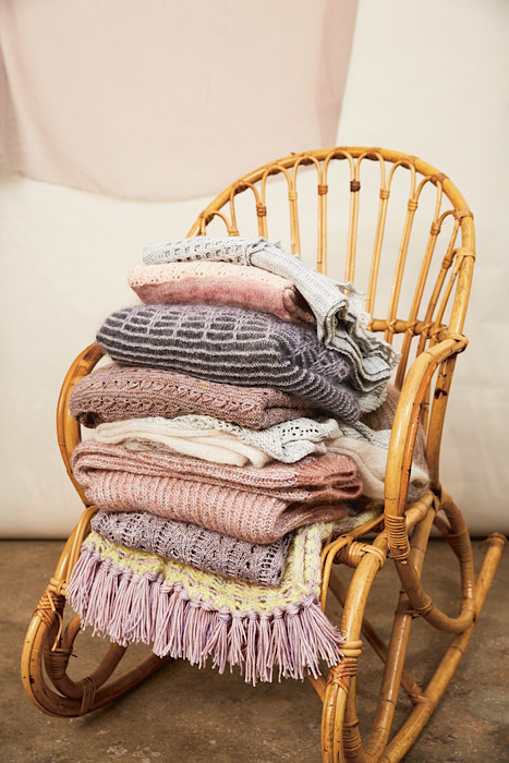 a knit pile on a rattan chair