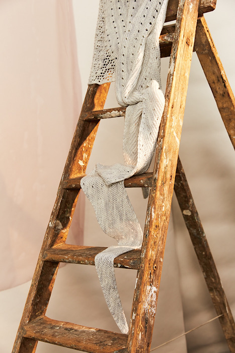 a still of a vintage ladder with a white knitted shawl draped over it