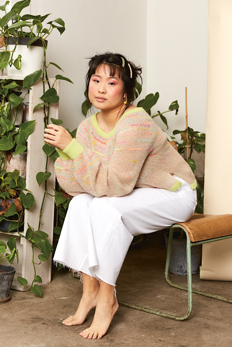 woman on a bench modeling a knitted sweater with neon accents on the background you see plants
