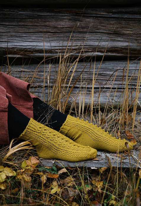 close up of model with yellow sock outside with dry grass on background